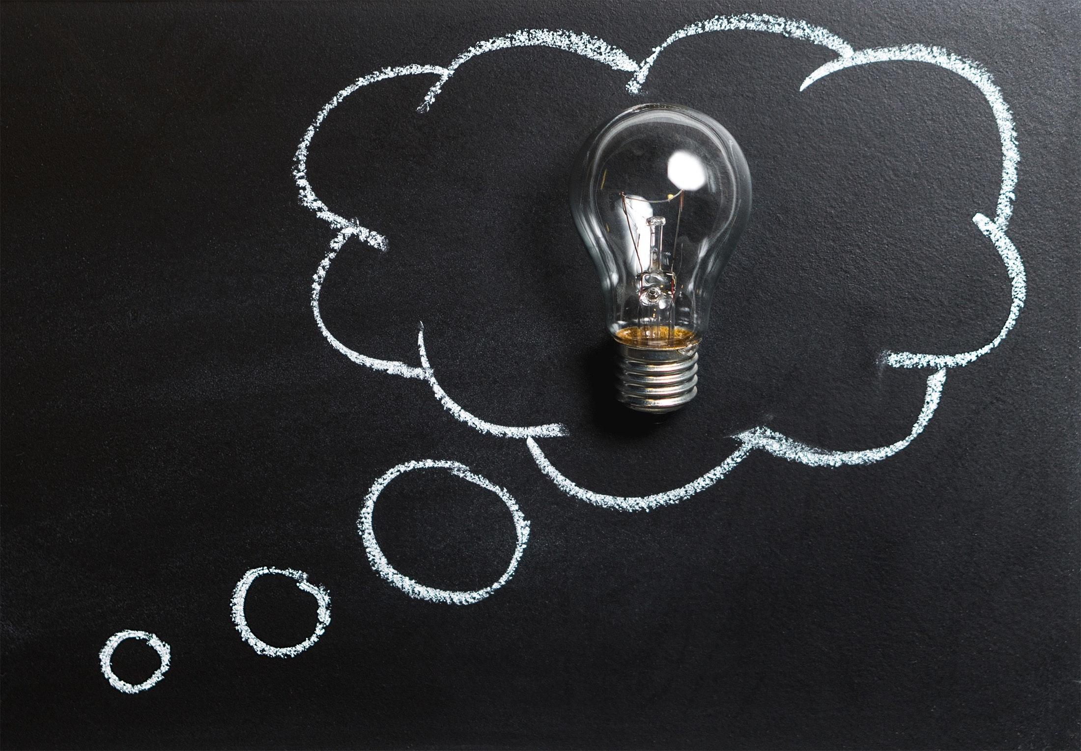 Lightbulb in chalk thought bubble on blackboard